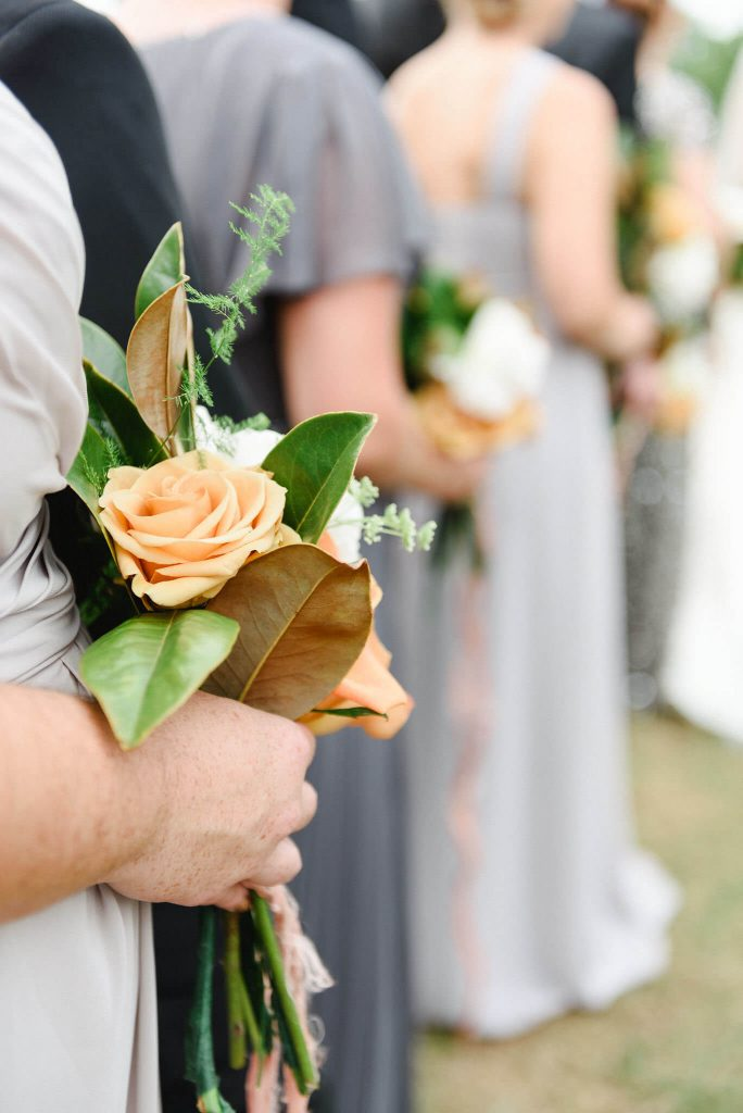 The bridesmaids cool gray dresses contrasted the rich copper tones in their bouquets.
