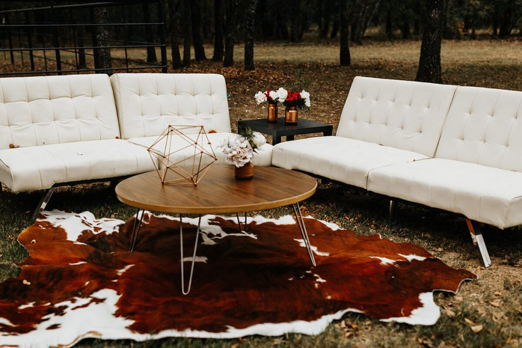 The outdoor lounge area included white leather couches and a cow-hide rug to create boho-chic wedding style ambiance.