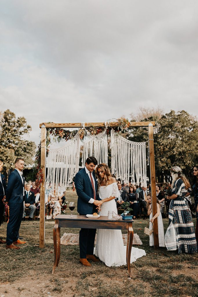 Hannah and Ryan stand beneath the alter in their outdoor boho-chic fall wedding ceremony.