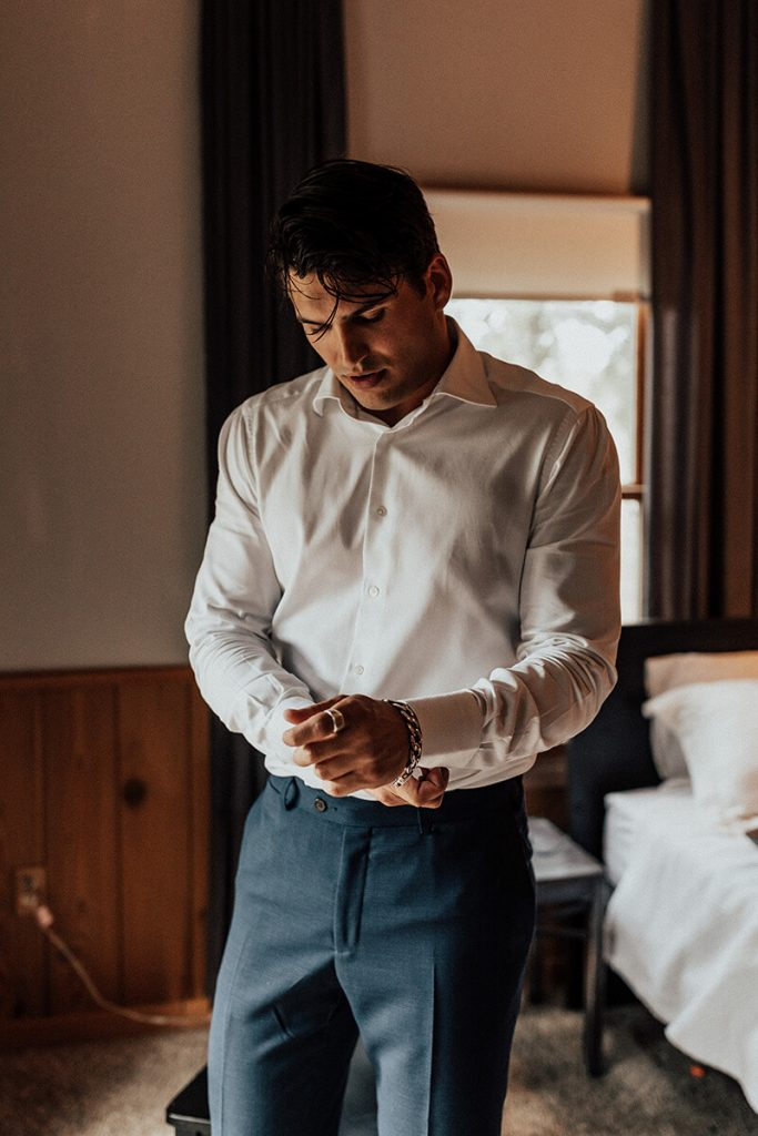 The groom gets ready for his boho chic fall wedding in our cabin at The Forge.