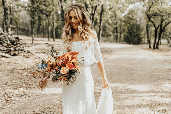 Boho Chic Fall Wedding bride Hannah poses in the open natural grounds of the wedding venue space.