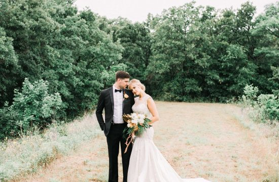 The bride and groom pose for a photo in the natural open landscape of the organic grounds of the Forge Wedding Venue