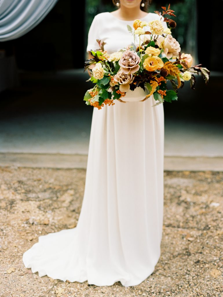The bride wears an elegant gown for this modern fall wedding photo shoot