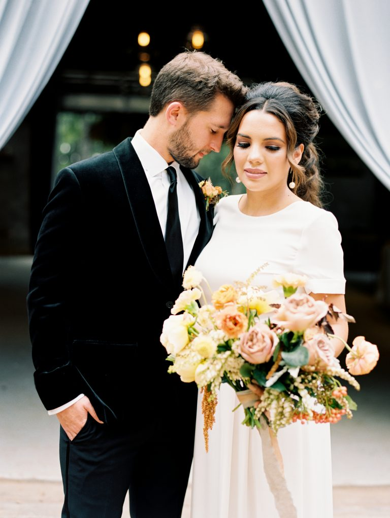 The bride and groom wear velvety warm fall style decorated with rustic colors and textures.
